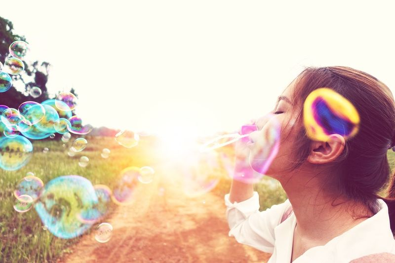 Girl blows bubbles Colorful Light Fun Headshot Bubble Portrait Blowing Multi Colored Young Adult Adult Nature Sky Happiness People Sunlight Outdoors Emotion Leisure Activity Lens Flare