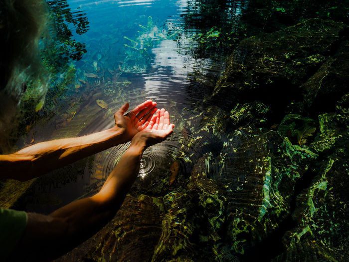 Cropped image of woman with hands cupped over lake