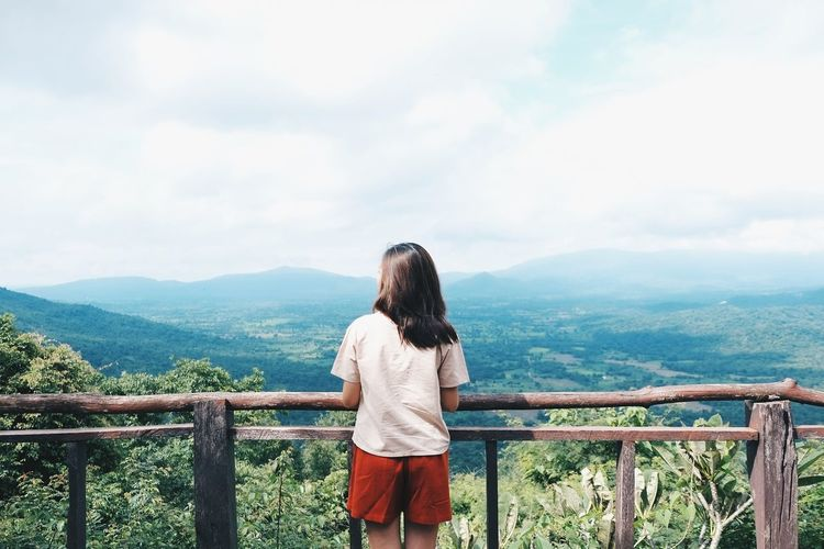 Rear view of young woman looking at landscape while standing by railing against cloudy sky