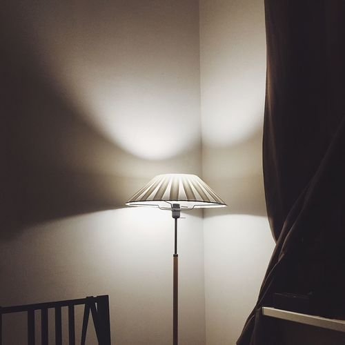 Close-up of illuminated electric lamp at home