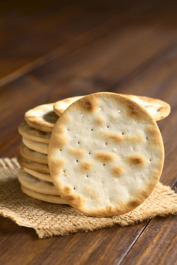 Saltine or soda crackers, photographed on dark wood with natural ight (Selective Focus, Focus on the standing cracker) Copy Space Crispy Snack Soda Baked Cracker Crackers Crisp Crunchy Dry Flat Food Food And Drink Pile Round Saltine Saltine Crackers Soda Cracker Stack Thin Vertical
