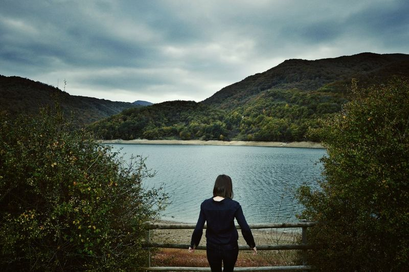Woman standing by lake against mountains