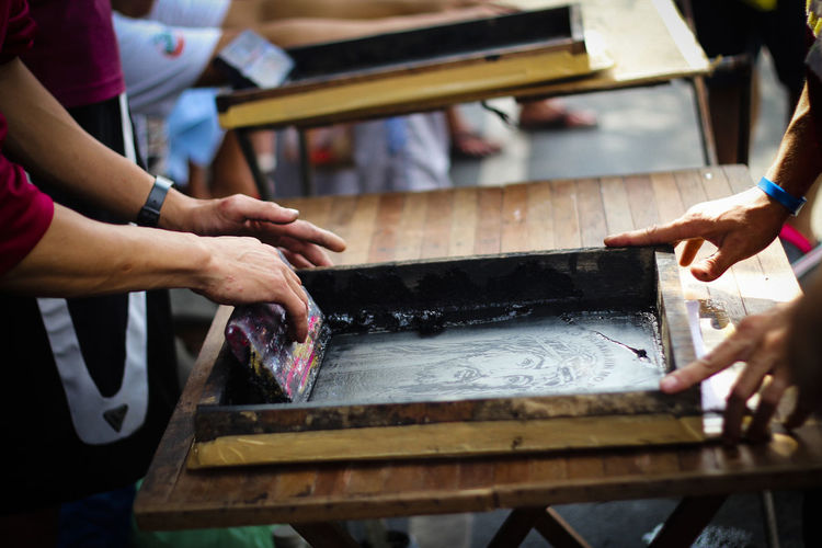 Cropped image of people screen printing at workshop