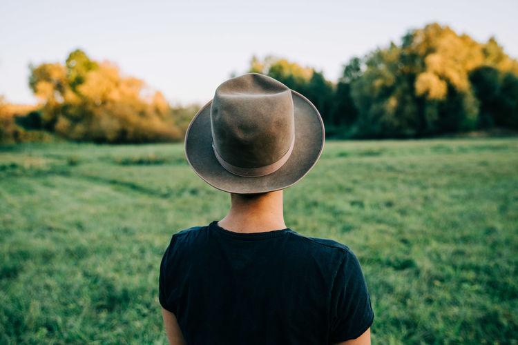 Rear View Of Teenage Girl Wearing Hat Against Grassy Field