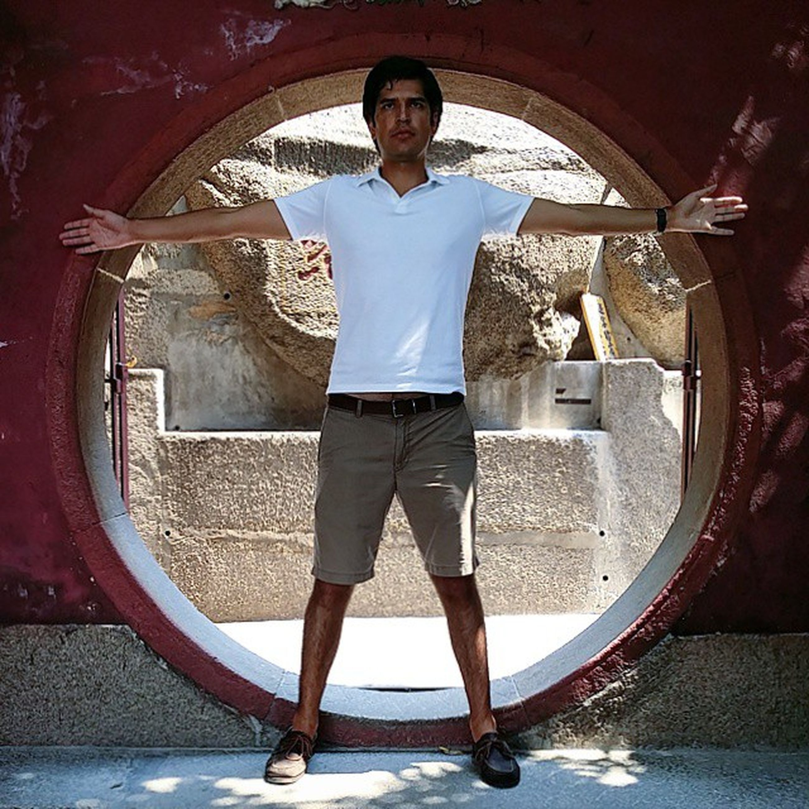 indoors, arch, standing, front view, casual clothing, lifestyles, looking at camera, portrait, leisure activity, architecture, full length, young adult, built structure, person, circle, day, door, archway