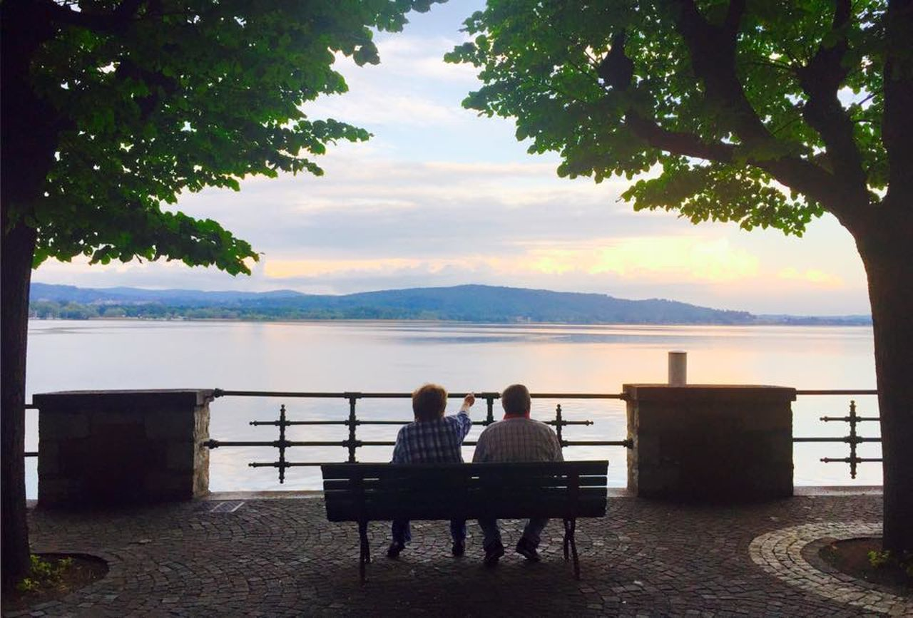 water, rear view, two people, sea, tree, scenics, nature, table, togetherness, sitting, leisure activity, tranquil scene, chair, relaxation, real people, looking at view, sky, tranquility, day, outdoors, beauty in nature, full length, women, men, horizon over water, friendship, adult, people