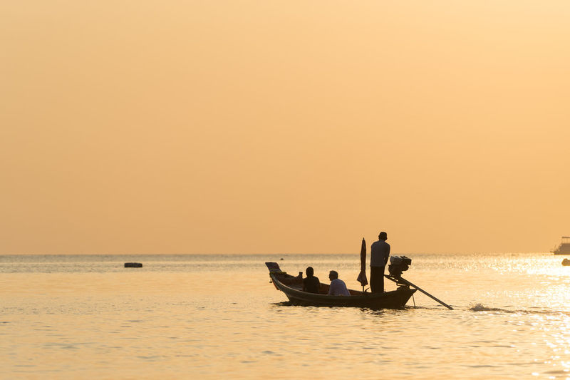 Silhouette people in boat on sea against sky during sunset