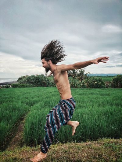 Side view of shirtless man jumping on grass against sky