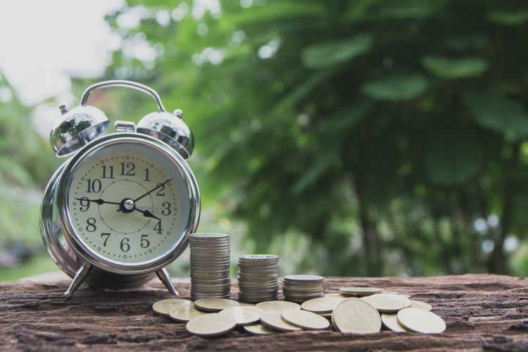 Close-up of alarm clock with coins on table