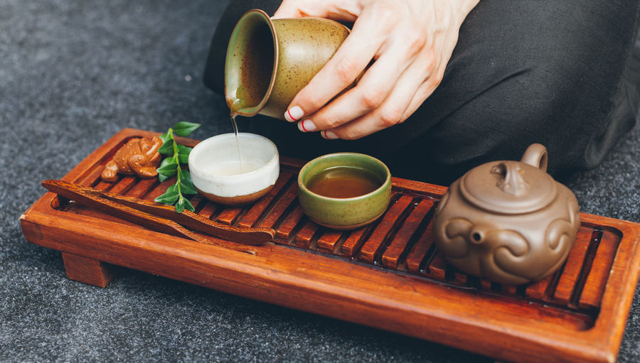 Cropped hand pouring tea in cup on table
