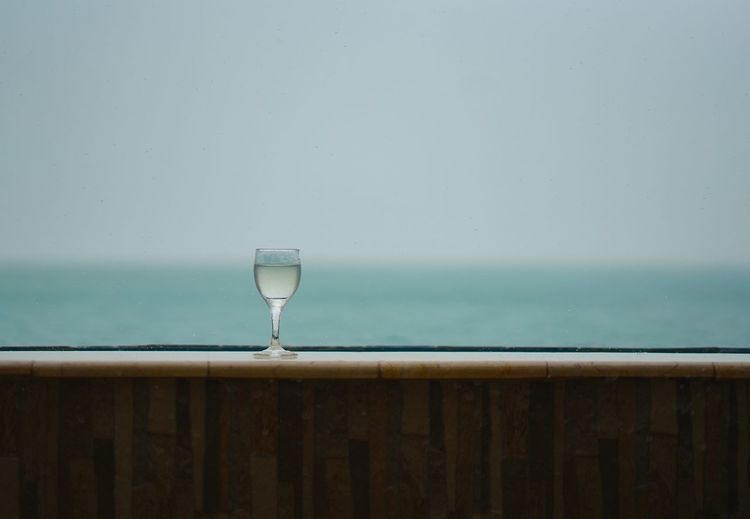 Wineglass On Table By Window Against Sea