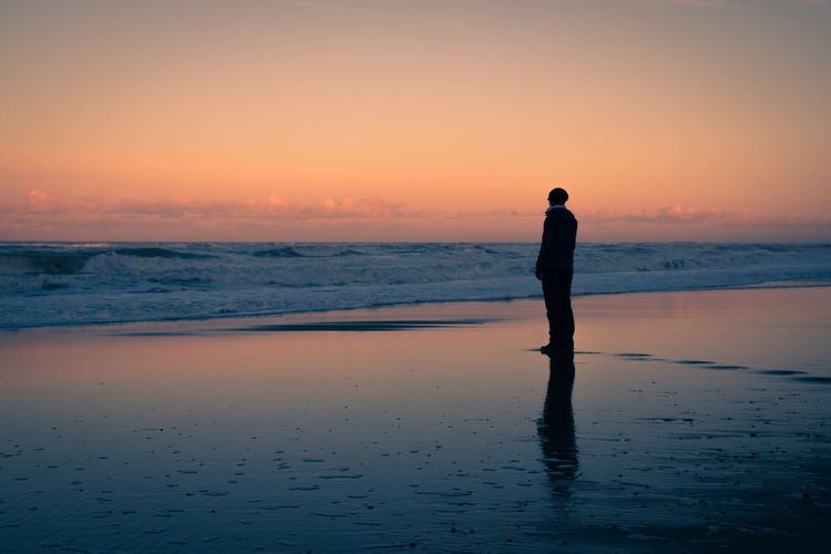 Silhouette Man Standing At Beach Against Orange Sky