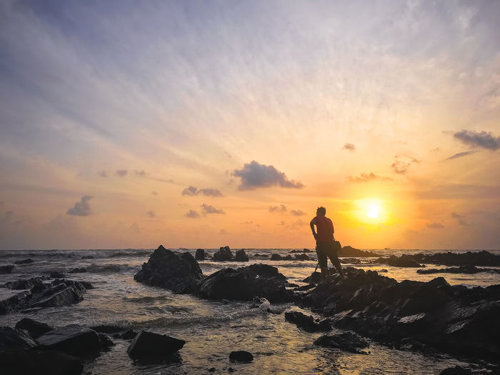Silhouette of young photographer on the beach Beach Beauty In Nature Day Full Length Horizon Over Water Leisure Activity Lifestyles Men Nature One Person Outdoors Real People Scenics Sea Shore Silhouette Sky Standing Sun Sunlight Sunset Tranquil Scene Tranquility Water Wave