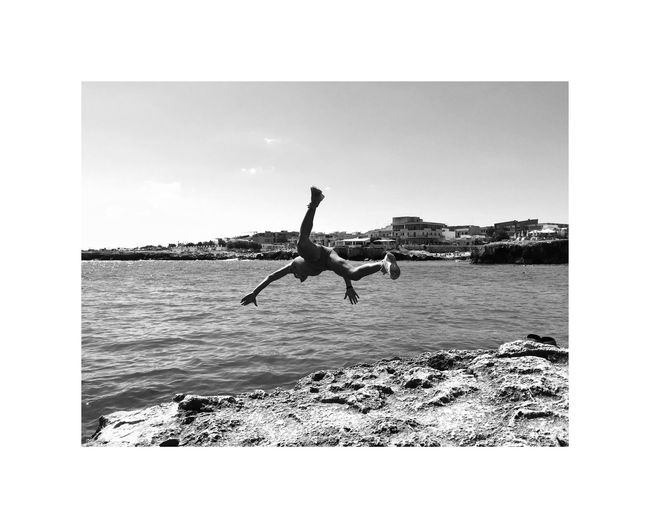 Men jumping on rock by sea against clear sky