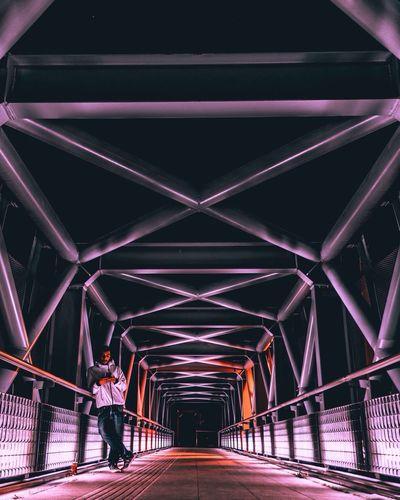 Full length of man standing on illuminated bridge at night