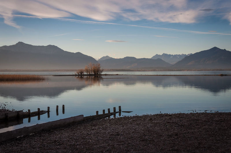 Scenic view of lake chiemsee by mountains against sky