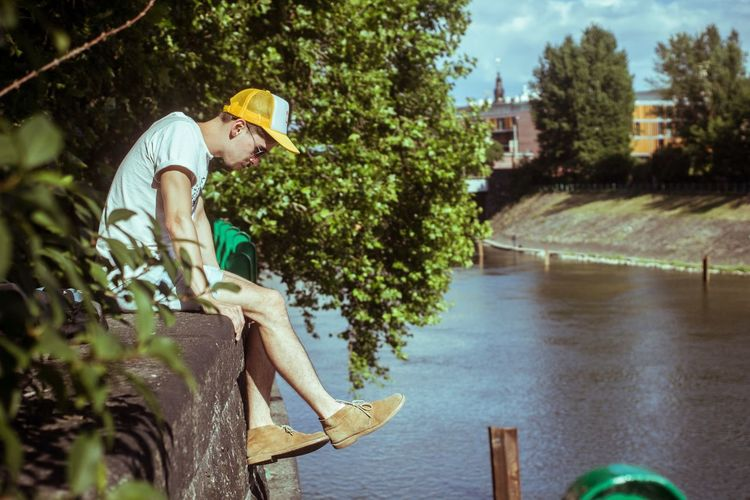 Side view of man sitting on retaining wall over river