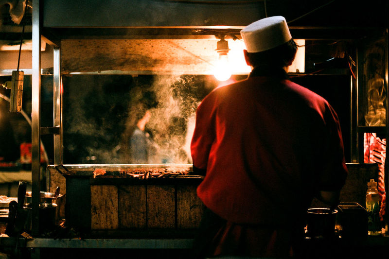 Kebab Peddler on Muslim Street in China Kebab Casual Clothing Dark Flame Glowing Heat - Temperature Illuminated Leisure Activity Lifestyles Night Smoke - Physical Structure Sunbeam