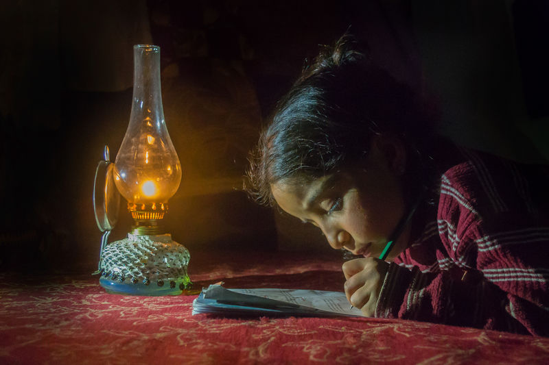 Side View Of Girl Writing On Paper By Illuminated Oil Lamp
