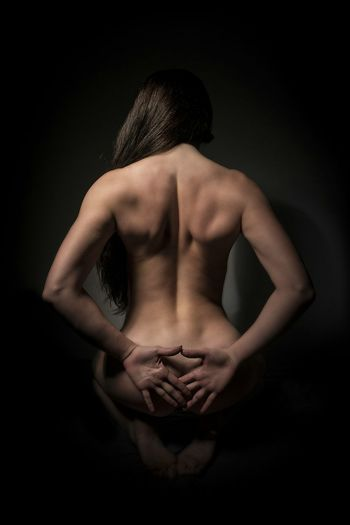 Rear view of sensuous naked woman in darkroom