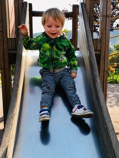 Cute boy smiling while sitting on slide