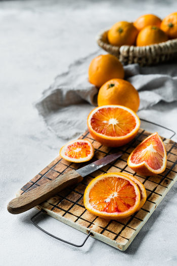 Blood oranges cutted in slices on a ceramic board   daylight food photography Food Food And Drink Healthy Eating Fruit Citrus Fruit Freshness Orange Color Cross Section SLICE Orange - Fruit Orange Halved No People Still Life Blood Orange Focus On Foreground Foodphotography Food Photography Nikonphotographer Daylight Photography Knife Grey Background