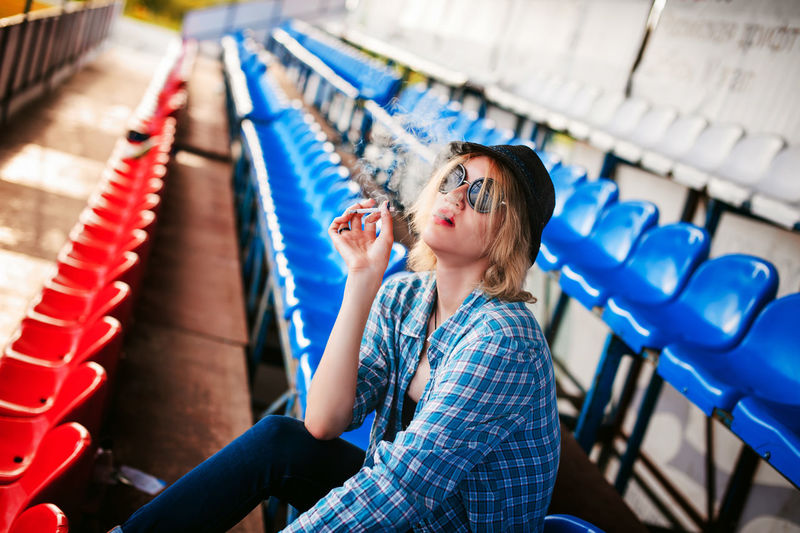 Young woman smoking cigarette on seat at stadium