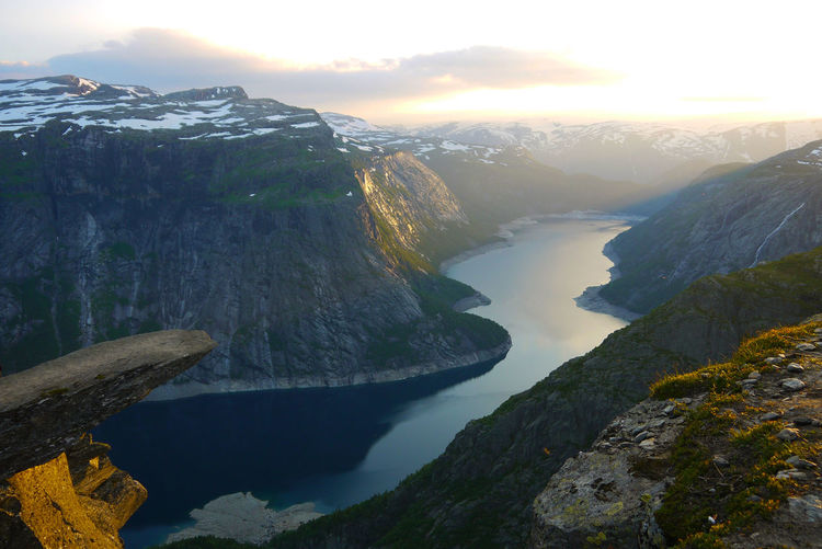 Trolltunga is a rock formation situated about 1,100 metres above sea level in the municipality of Odda in Hordaland county, Norway Landscape Travel Destinations Beautiful Scenics Scandinavia Europe Cliff Famous Snow Sunset Sunlight Day Norway Wallpaper Colorful Trolltunga Hike Sky Mountain Scenics - Nature Beauty In Nature Water Tranquil Scene Tranquility Fjord Rock Mountain Range Nature Rock - Object Solid Non-urban Scene No People Idyllic Environment Outdoors