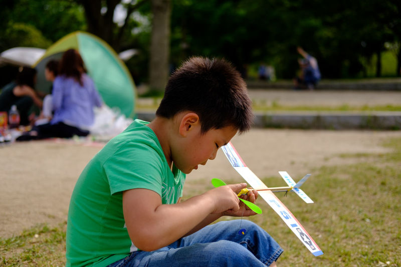 Boy playing with toy airplane at park