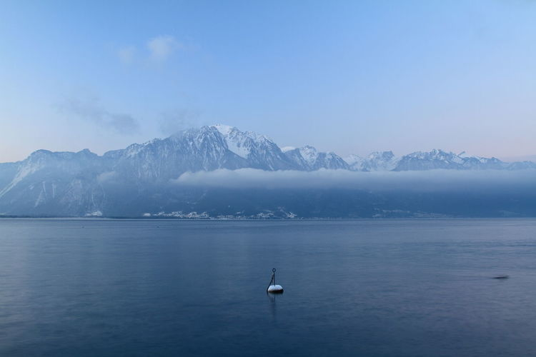 Scenic view of lake geneva and snowcapped mountains against sky