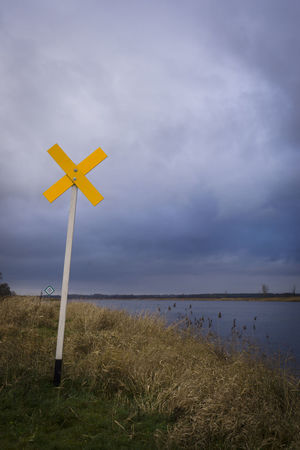 Yellow sign, Oderbruch (Brandenburg, Germany) Beauty In Nature Cloud - Sky Contrast Dark Dramatic Sky Environmental Conservation Horizon Over Water Landscape Nature Not Outdoor Outdoors Remote Rural Scene Sea Sky Tranquility Walking Around Warning Sign