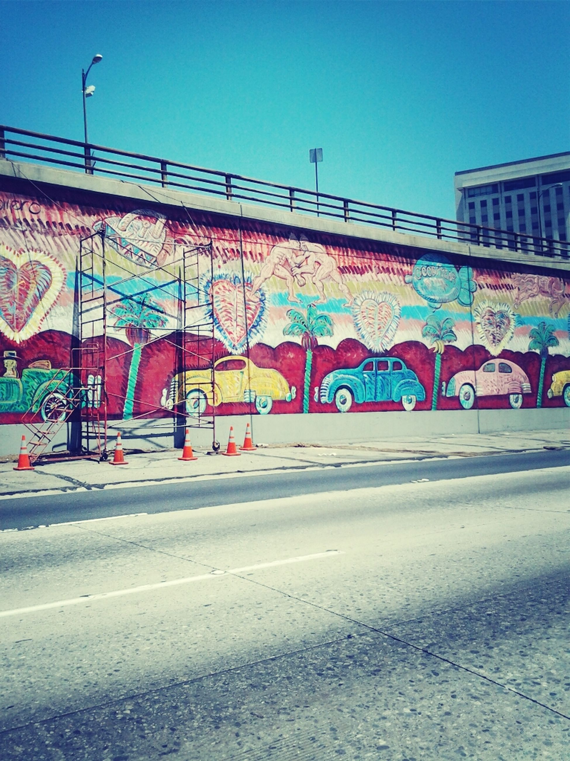 graffiti, art, creativity, art and craft, architecture, built structure, text, multi colored, street art, building exterior, human representation, wall - building feature, western script, blue, street, communication, road, outdoors, clear sky, transportation