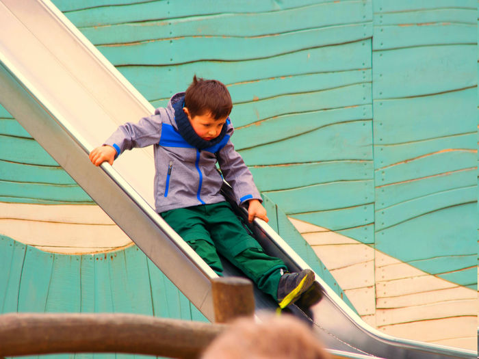 Cute boy playing on slide