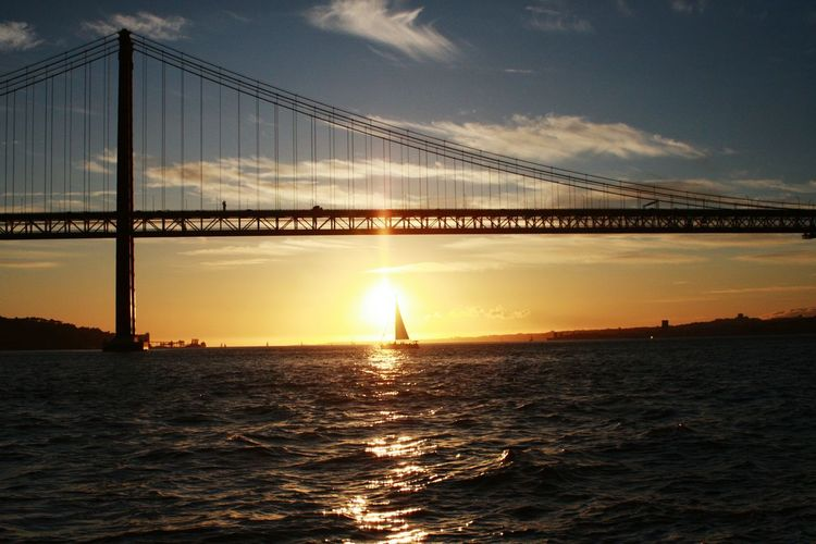 Sunset Sea Sky Cloud - Sky Water Bridge - Man Made Structure Architecture Suspension Bridge Reflection Sun Outdoors Transportation Built Structure Bridge Over Water Bridge Architecture_collection Tejo Tejo River River View River Architectural Feature Architecture Engineering Connection Yacht Be. Ready. Summer Exploratorium Adventures In The City