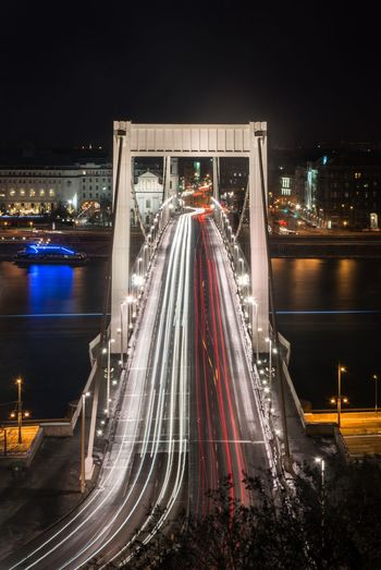 High angle view of light trails on chain bridge at night