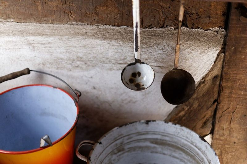 High Angle View Of Ladles And Buckets By Wooden Wall