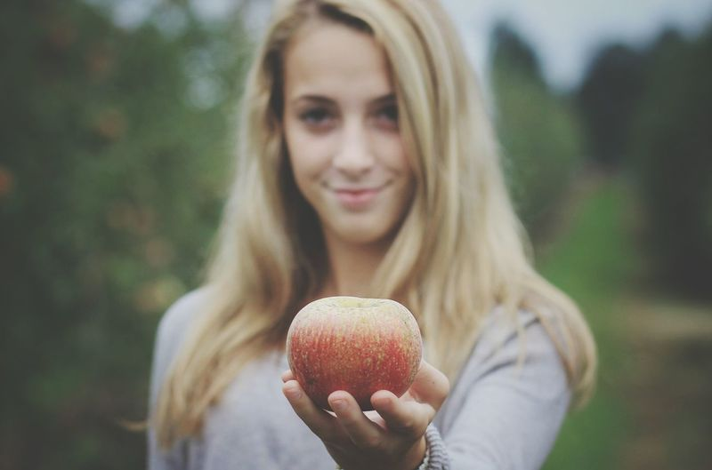 Portrait of smiling young woman holding apple