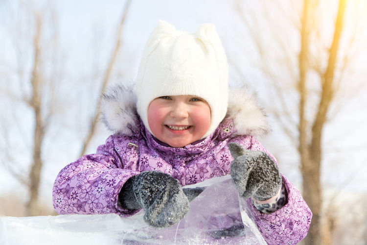 Portrait of smiling cute girl playing with ice while standing outdoors