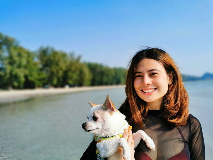 Portrait of smiling young woman holding dog against sea