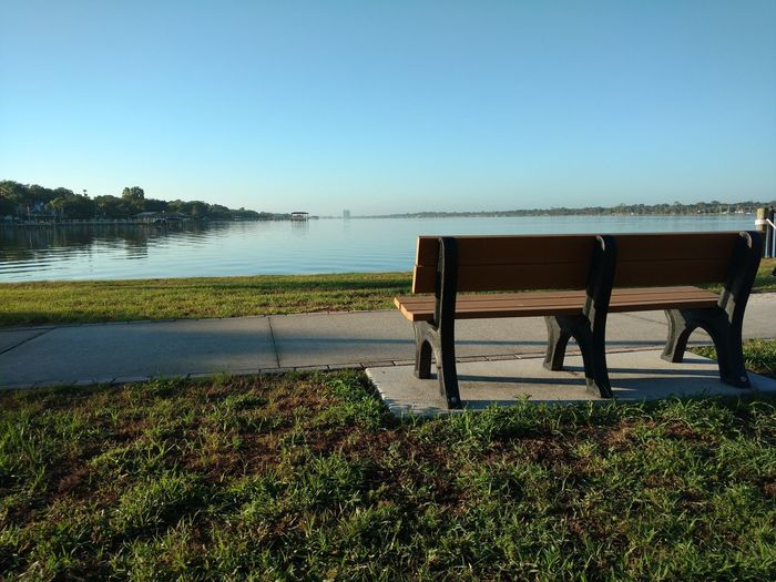 Bench in park by lake against clear sky