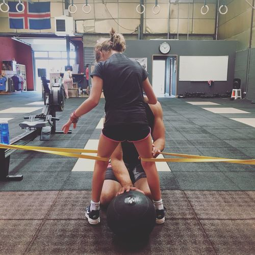 Rear view of girl following trainer instructions in gym