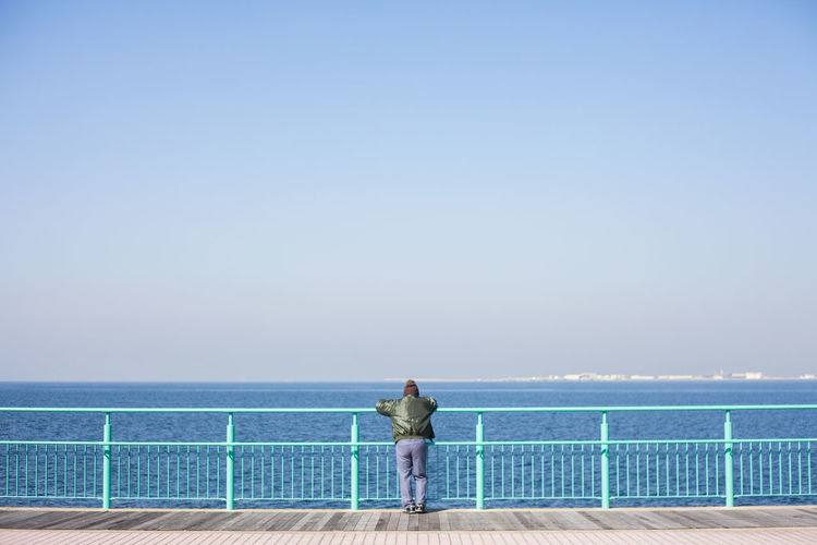 Rear view of man standing on railing against sea and sky