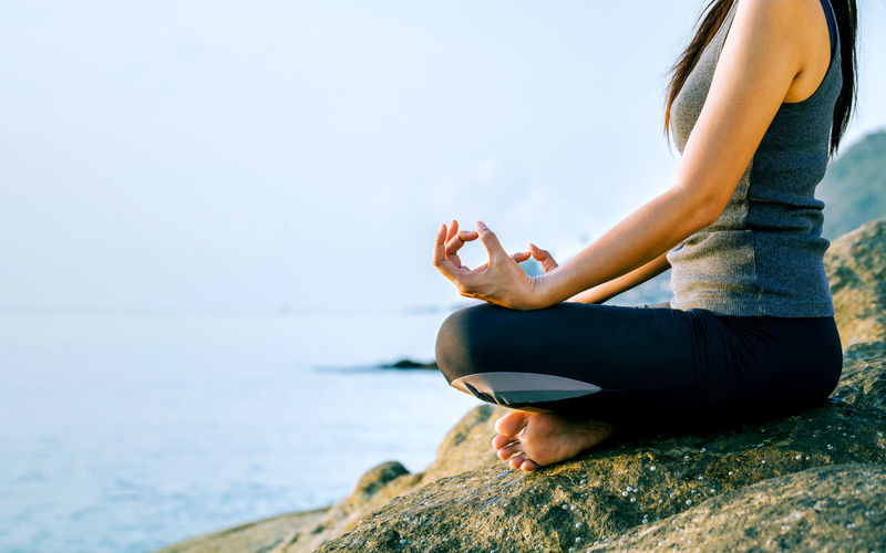 Young Woman In Lotus Position On Shore
