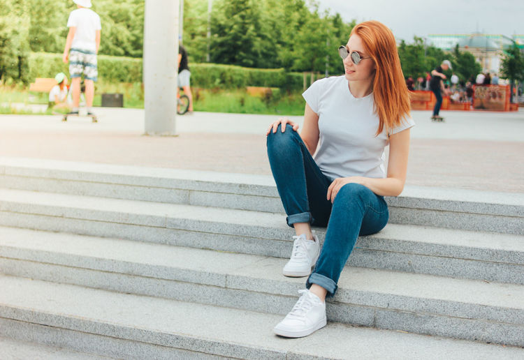 Smiling young woman looking away while sitting on steps