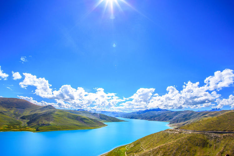 High Altitude Valley Beauty In Nature Blue Bright Climate Change Cloud - Sky Environment High Altitude Idyllic Lake Landscape Lens Flare Mountain Mountain Range Nature No People Non-urban Scene Outdoors Scenics - Nature Sky Sun Sunlight Tibet Tranquil Scene Tranquility Water