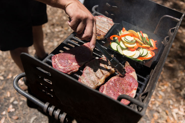 Low section of man preparing meat on barbecue grill
