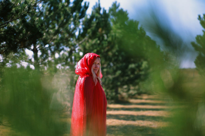 Trees Evergreen Tree Pine Tree Red Riding Hood Little Red Riding Hood Big Bad Wolf Pursuit - Concept Prey Victim Woman Girl Beautiful Woman Blonde Blonde Girl Blond Hair Red Cloak Hood Shawl Countryside Rural Scene Rural Rural America Farm Ranch Plains Prairie Great Plains One Person Day Clothing Standing Outdoors Selective Focus Smile Smiling Seductive