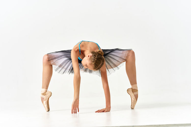 Full length of ballet balancing over white background