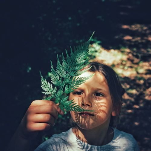 High Angle View Of Girl Holding Leaf While Standing Outdoors
