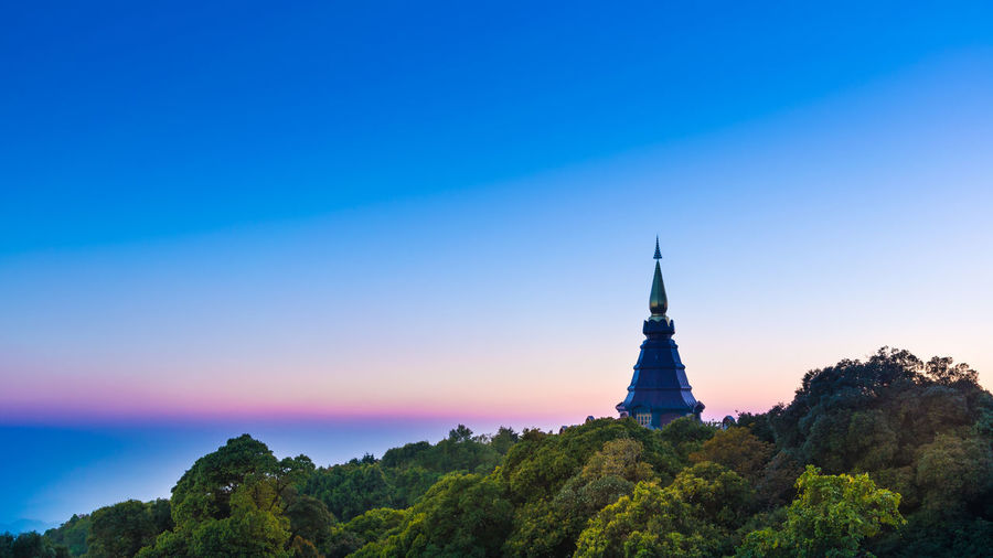 Landscape of pagoda on the top of Inthanon mountain and Evergreen forest location at Doi Inthanon National Park Chiang Mai Thailand 2-2015. National Park Architecture Blue Blue Sky Building Building Exterior Built Structure Clear Sky Copy Space Forest Mountain Nature No People Outdoors Place Of Worship Plant Religion Scenics - Nature Sky Spire  Spirituality Tower Travel Travel Destinations Tree
